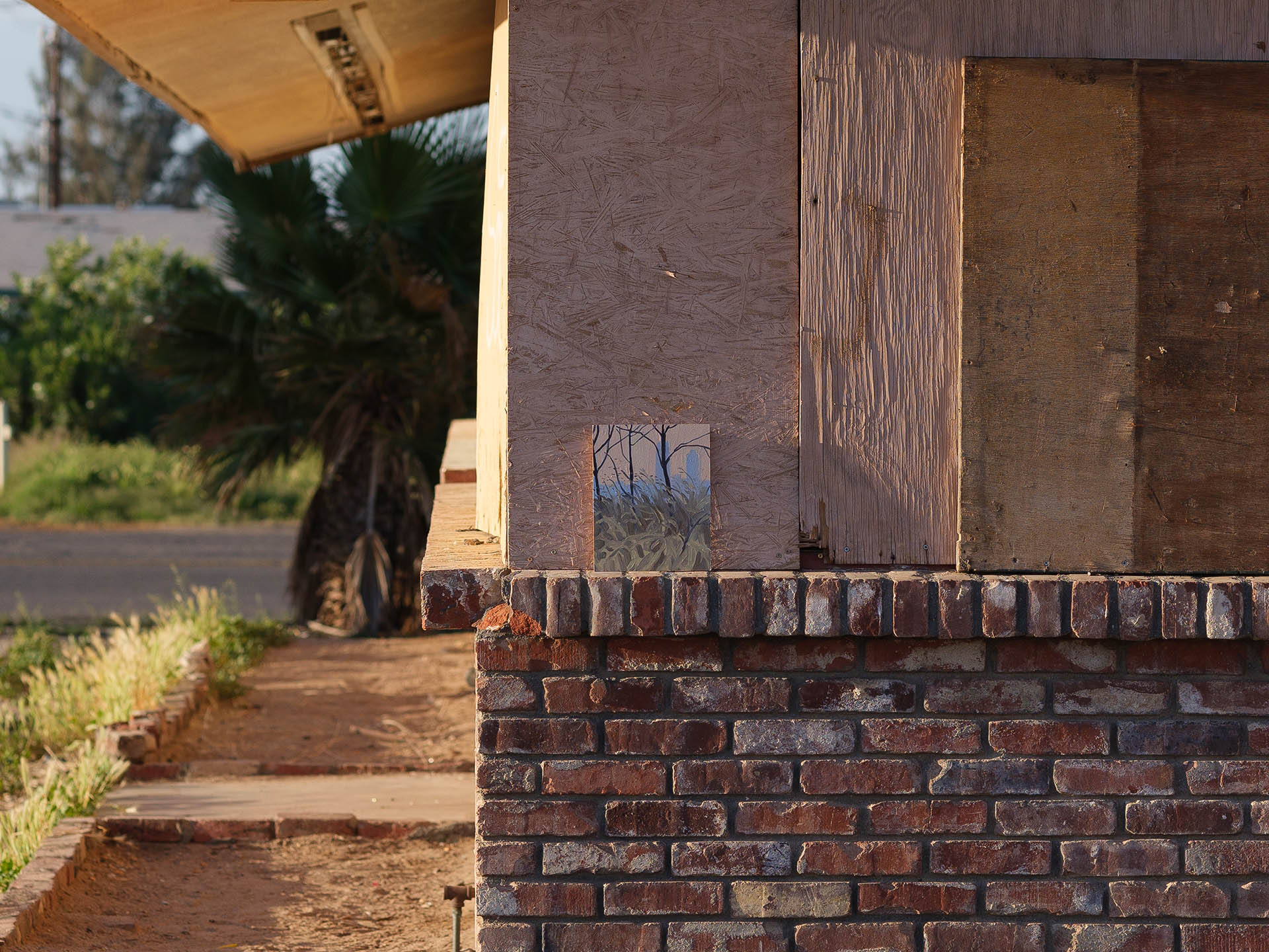 An installation view of Claudia Keep's painting, Sunset, Domino Park, captured by photographer Tag Christof in the Western United States in 2021 for MARCH. The image shows a painting sitting against a brick and wood facade.