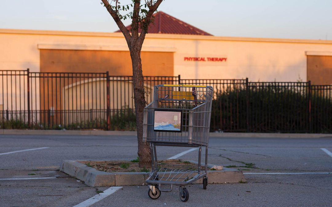 An installation view of Claudia Keep's painting, September Morning, captured by photographer Tag Christof in the Western United States in 2021 for MARCH. The image shows a painting hung outside on a shopping cart.