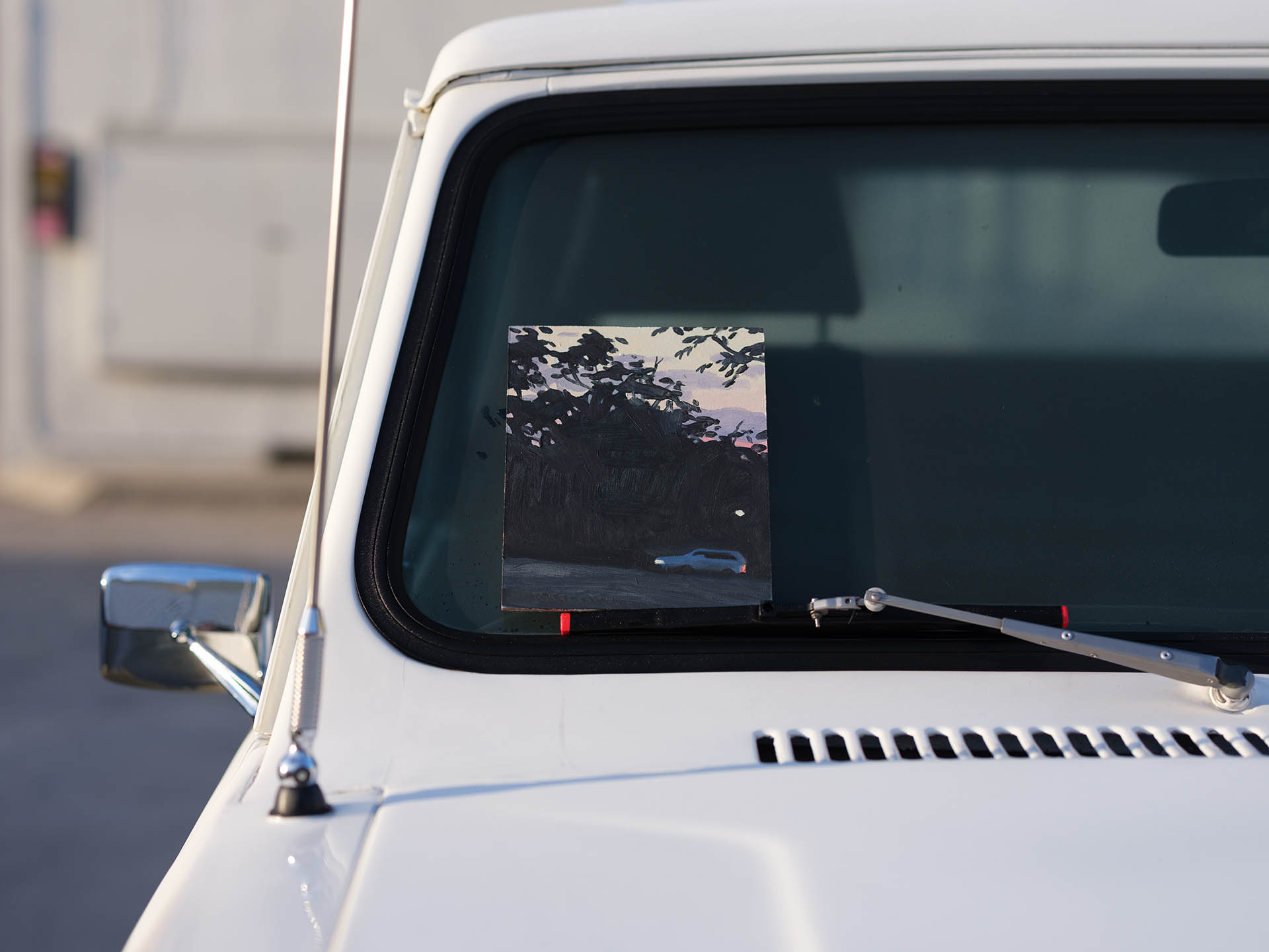 An installation view of Claudia Keep's painting, Driving Uphill, Early Evening, captured by photographer Tag Christof in the Western United States in 2021 for MARCH. The image shows a painting sitting in the windshield of a white car.