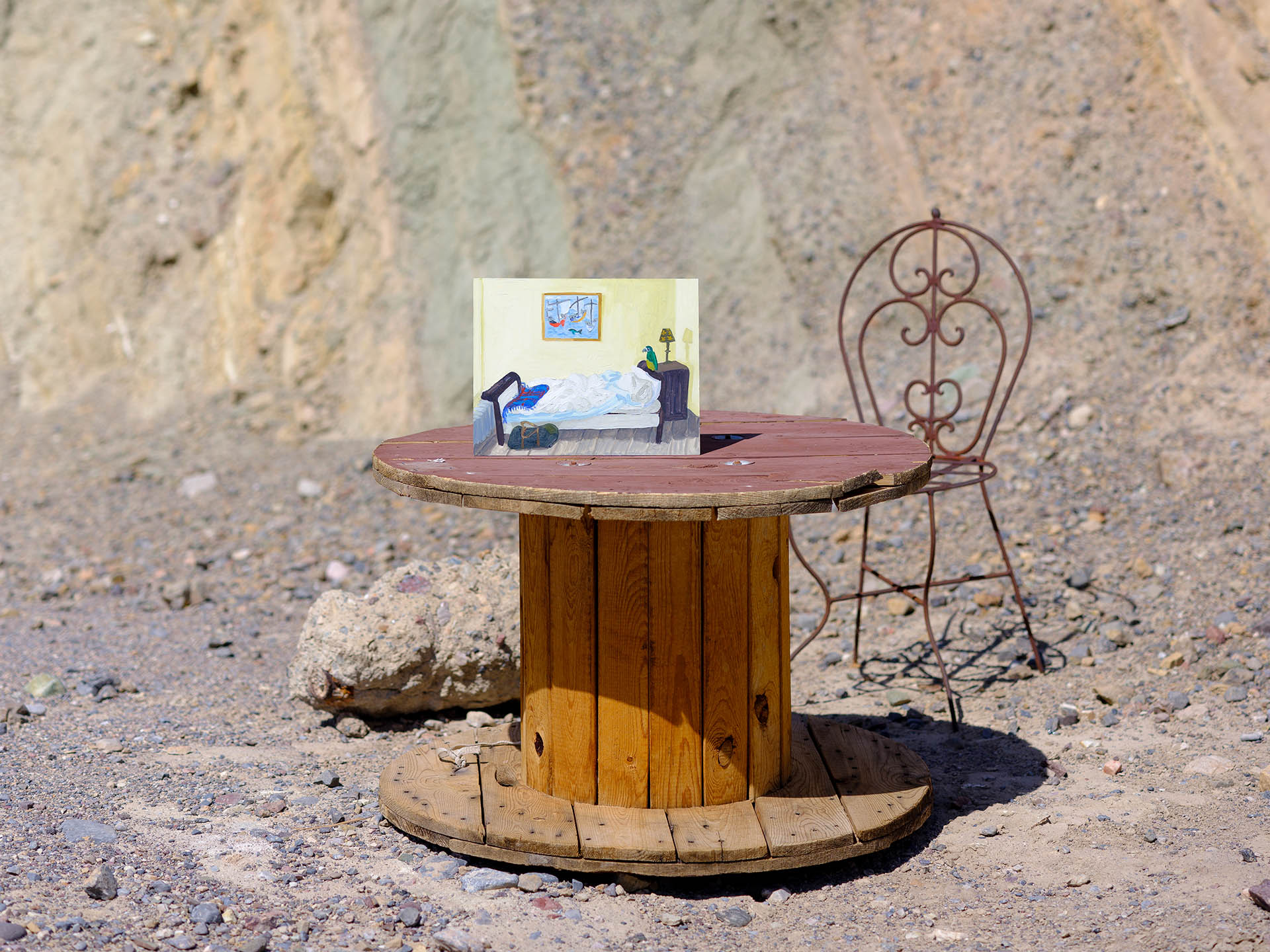 An installation view of Claudia Keep's painting, L'Enfance, captured by photographer Tag Christof in the Western United States in 2021 for MARCH. The image shows a painting sitting on a table in the desert.