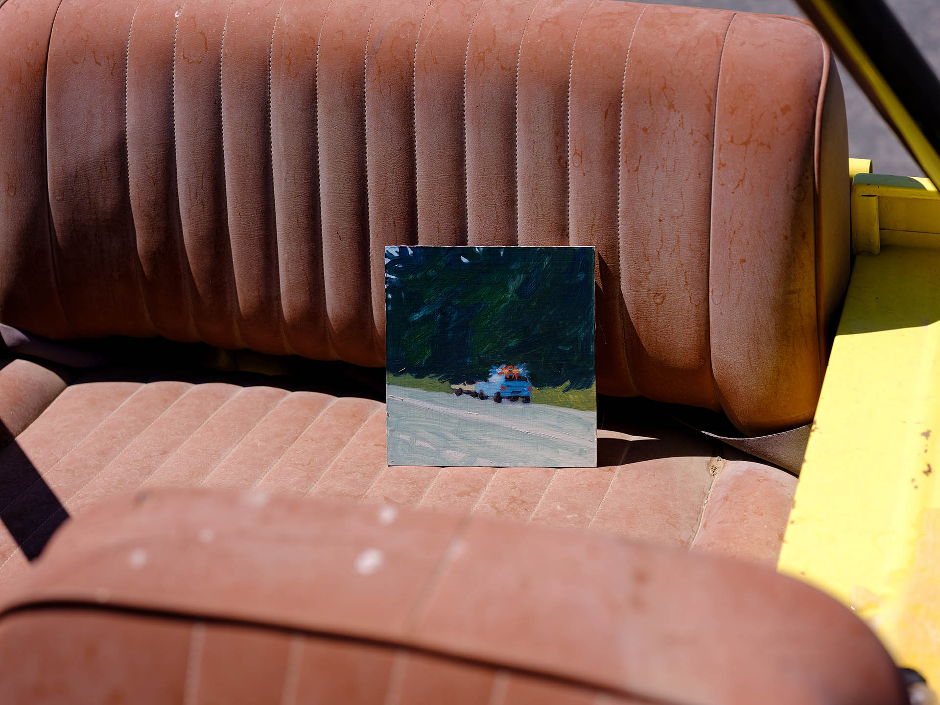 An installation view of Claudia Keep's painting, Staties, captured by photographer Tag Christof in the Western United States in 2021 for MARCH. The image shows a painting sitting in the backseat of a car.
