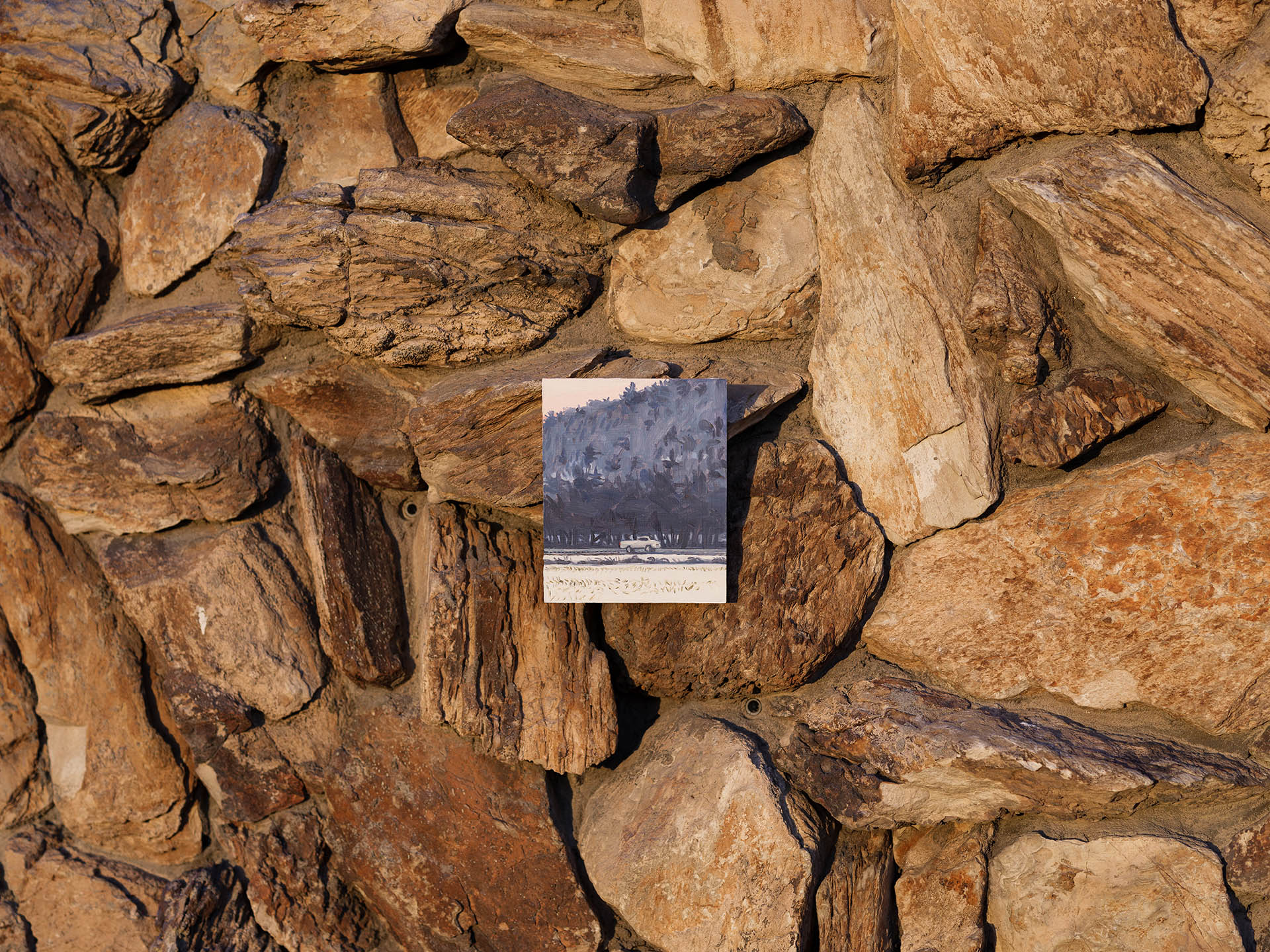 An installation view of Claudia Keep's painting, Driving to Richmond, captured by photographer Tag Christof in the Western United States in 2021 for MARCH. The image shows a painting laying on a bed of stones.