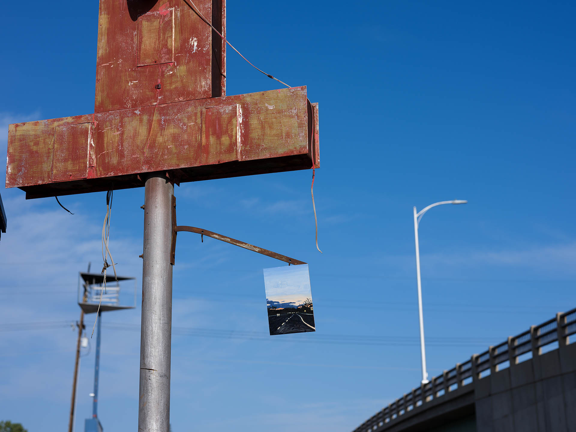 An installation view of Claudia Keep's painting, Missed Exit, captured by photographer Tag Christof in the Western United States in 2021 for MARCH. The image shows a painting hung on a sign.