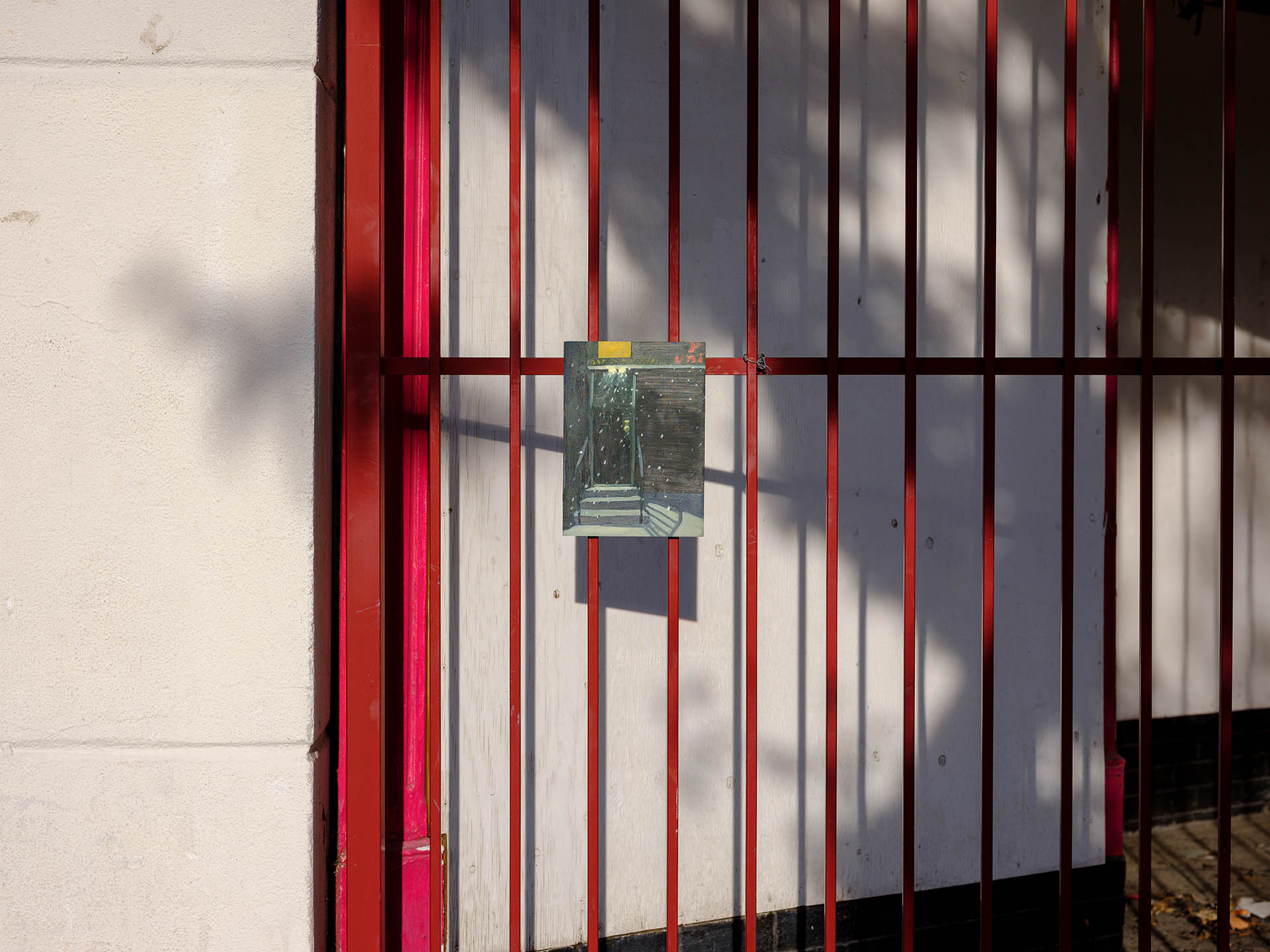 An installation view of Claudia Keep's painting, St. Nicholas Ave., captured by photographer Tag Christof in the Western United States in 2021 for MARCH. The image shows a painting hung outside on a red gate.